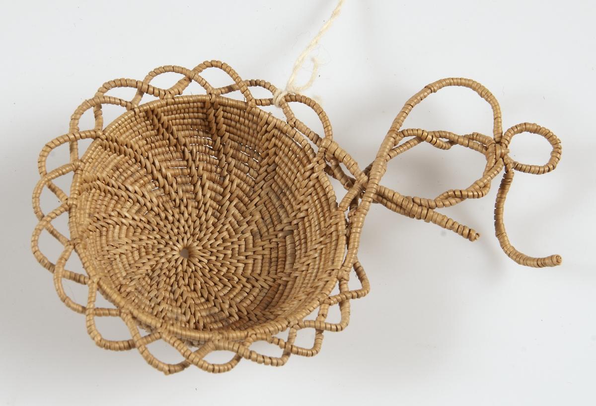 Tesil av bundna björkrötter i mycket tunn kvalitet, s. k. tesilsrötter. Tesilen är rund med virvelmönster, uddkant och hjärtformat handtag av lindade rötter. Tillverkad av Gertrud Nilsson.