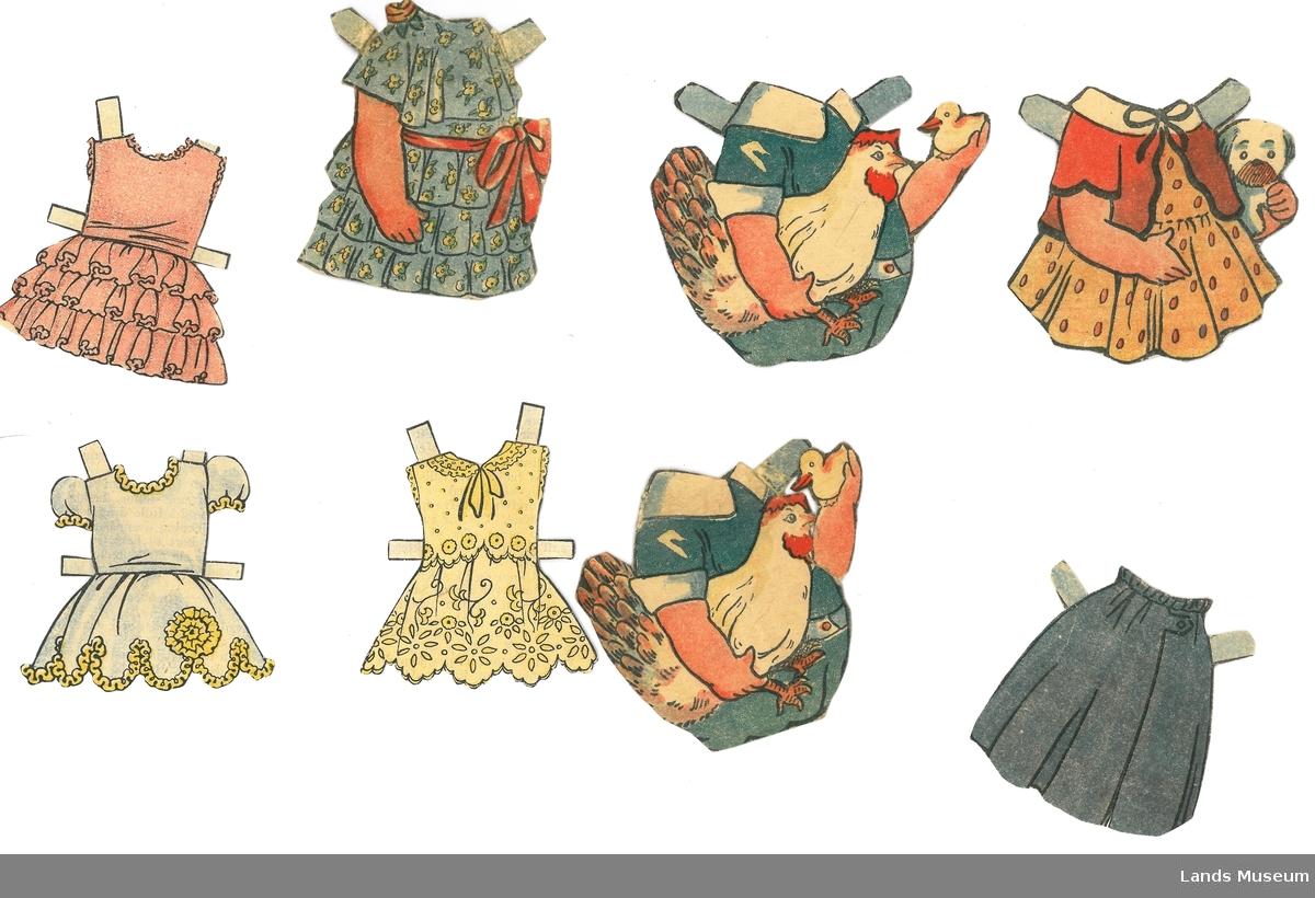 Samling av klær til papirdukke, nokre er klipt ut frå avis/magasin, andre (B, C, D) er klipt ut frå utklippsark.  A- kjole, grønn med rødt belte, 7,5 x 6,5 cm B- kjole, kvit med gul pynt, 6 x 6 cm C- kjole, kvit med gult broderi, 6,5 x 6 cm D- kjole, rosa med knapper, 6,5 x 6,5 cm E- skjørt, blått, 6,5 x 6,5 cm F eks.1 og F eks.2- drakt, blå med høne og kylling, 8 x 9,5 cm G- kjole, gul med prikker og rød jakke, 7 x 7 cm