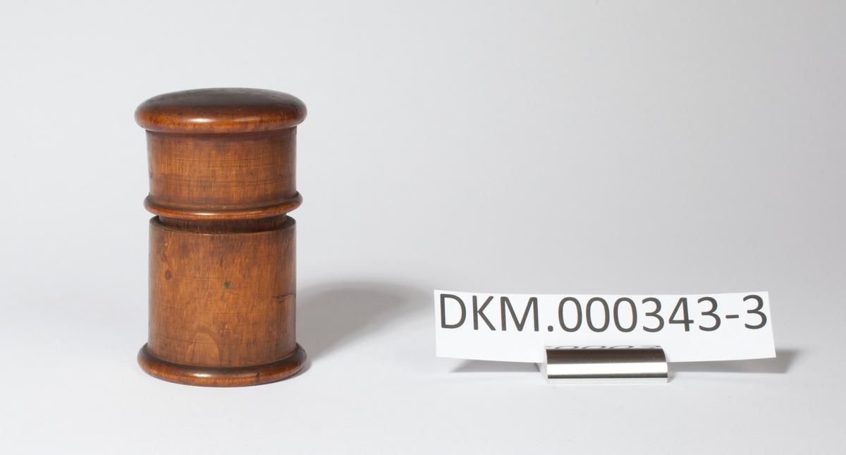 Rund brunbeiset boks med lokk av dreid bjørk. Brukt til å oppbevare bokstavtyper.