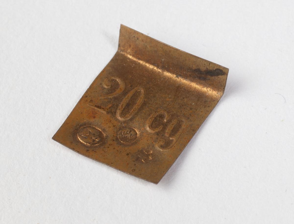 Ett tynt, rektangulært platelodd.