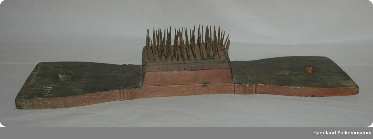 Rektangulær treplate som er noe innsnevret på midten. Et hull i hver ende fungerer som håndtak. Midt på platen er det to mindre rektangulære trestykker som danner base for en firekantet metallplate med jernpigger som står opp. Rester etter dekor.