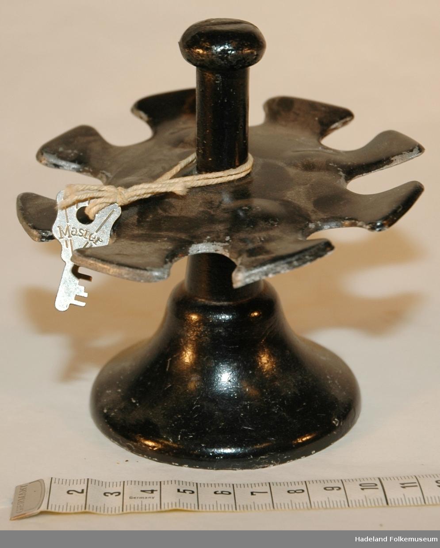Form: rund fot med rund plate oppå med hull til å henge stempler