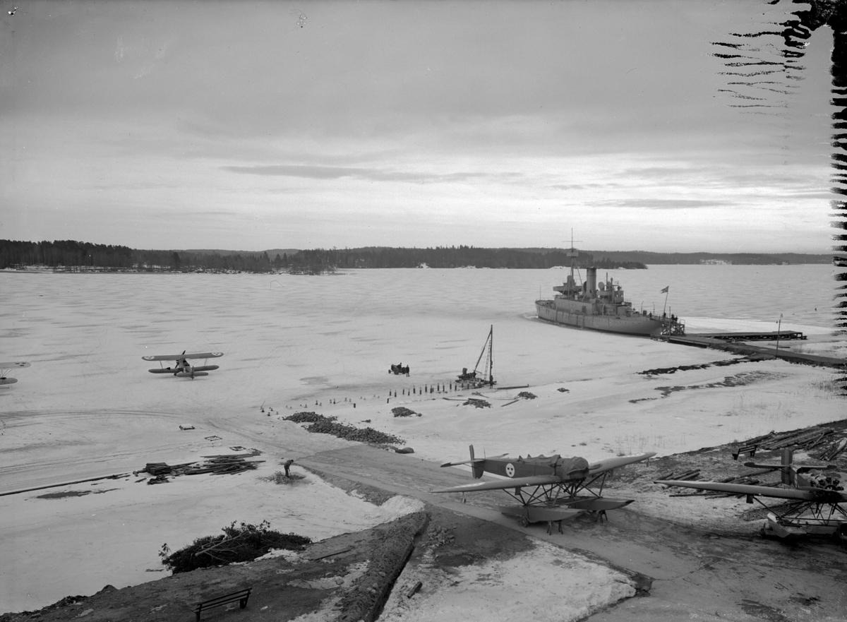 Översikt av brygga och slip på F 2 Roslagens flygflottilj vintertid, 1934. Personer i arbete med pålningsarbete för brygga. På isen står ett miltärt flygplan och fartyget HMS Göta. I förgrunden syns två flygplan S 5.