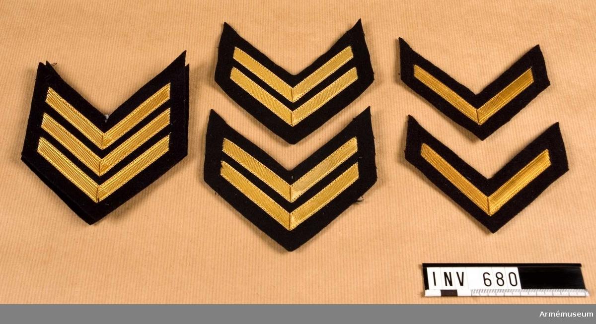 Gradbeteckning, Marinen.Består av: 1 st förvaringslåda (trasig pappkartong som ej tillhör   föremålen, kastad 1990-08-31 av Maria Petterssson), 100 st gradbeteckningar för flaggkadett, tre streck, (kod 7674-651000-3), 100 st gradbeteckningar för kadett/sergeant, två streck, (kod 7674-652000-2), 100 st gradbeteckningar för kadett furir, ett streck, (kod 7674-653000-1). Vinklarna sitter på vänster överarm och tecknar V:n.Föremålen finns men är ej räknade i samband med förberedelser   för flyttningen / 1990-08-31 Maria Pettersson.DEP  1994-08-16: En beteckning av var typ sparade och  magasinerade. Övriga deponerade hos Marinmuseum.