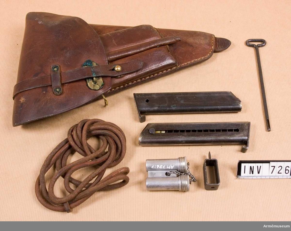 Samhörande nr är 725-26.Fodral t pistol m/1940.Består av: 1 pistolfodral, 1 pistolsnodd, 2 st extra magasin m/1940, 1 läskstång, 1 magasinsfyllare, 1 oljedosa.