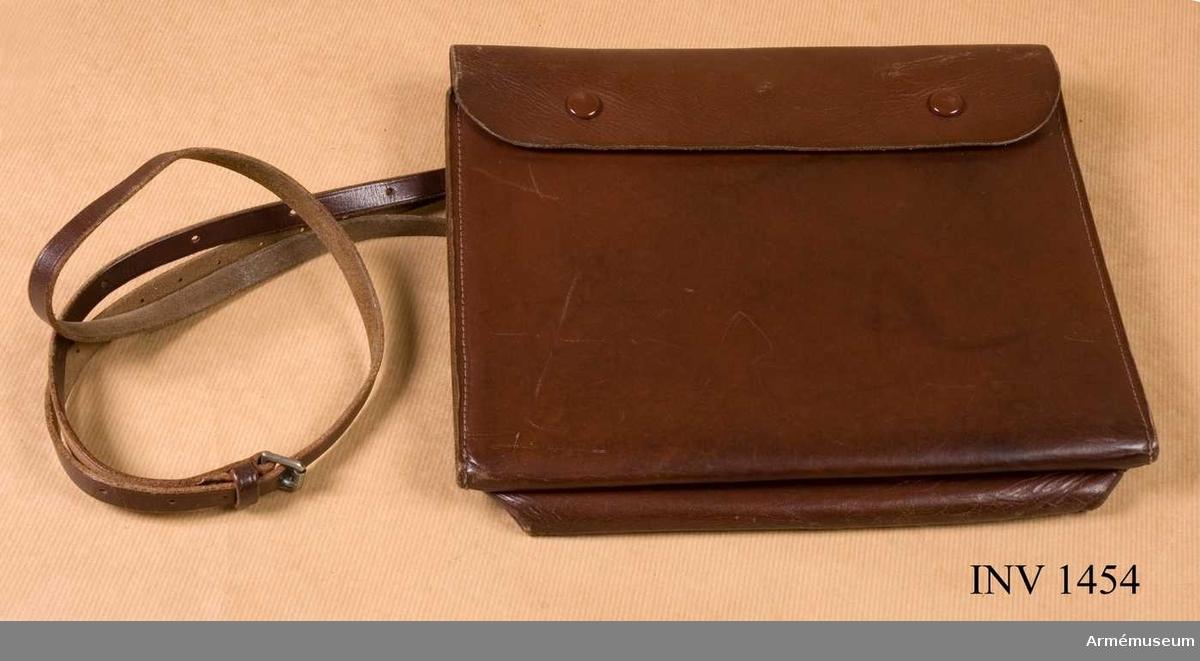 """Samhörande nr är 1454-1473.Kartfodral m/1915, officer.Av brunt läder. Knäppt med två tryckknappar, märkta """"Haania"""". Har två fack, ett för pennor m m och ett för kartor. På baksidan två ringar för fastsättning av en smal, ställbar rem för bärande över axeln."""