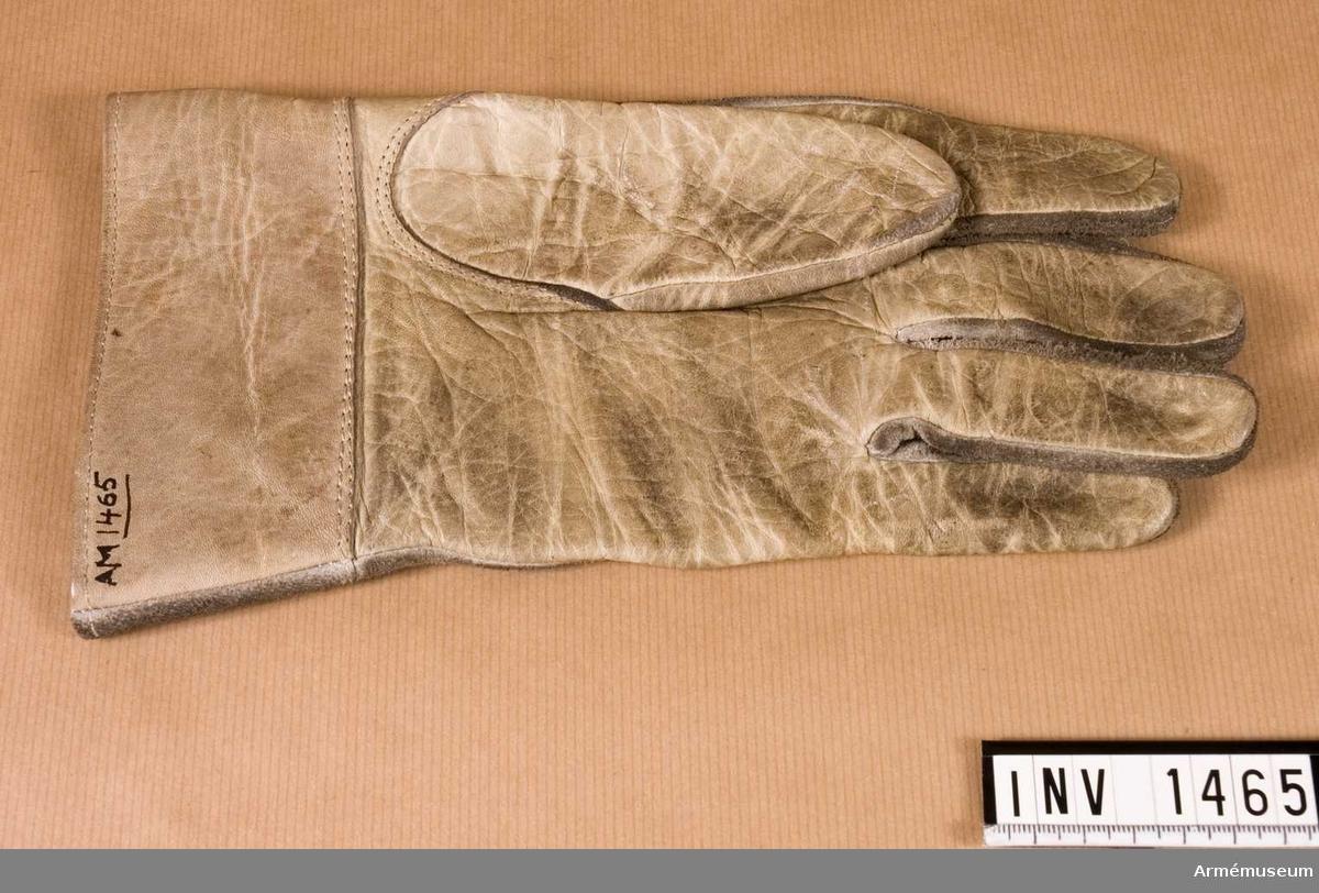 Handske m/1938, ytter-, Vänster. Av vitt skinn, blankt på handens innersida. Vid handleden en 55 m hög krage.