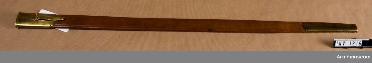 Av brunt läder med beslag av mässing; det övre försett med koppelkrok av samma material. Inköpt av skriftställare I Orre. Samhörande nr är 1915-1916.
