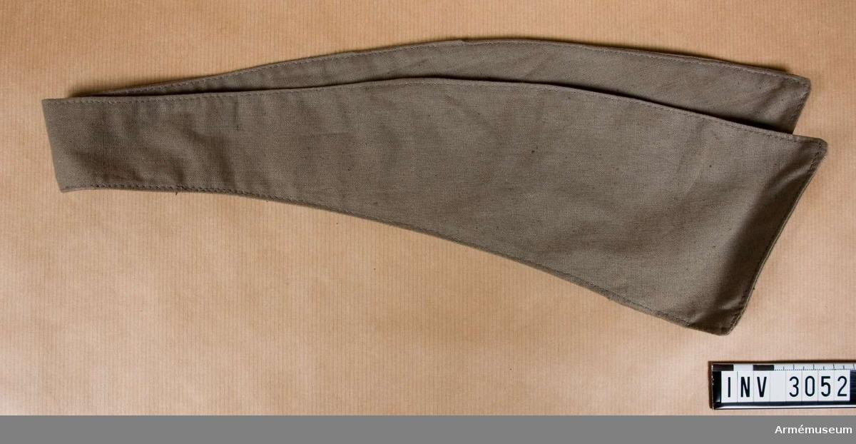 Av gråbrungrönt bomullstyg. Något svängd och avsmalnande mot mitten. Uddarna är 100 mm breda och bredd mitt bak 450 mm. På avigan en slå av tyget, fastsatt på skrådd. Häri skall man trä den motsvarande slipsänden. Buren av överste A Hallström.