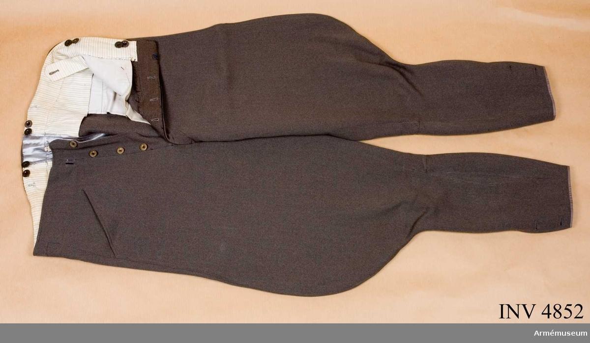 """Storlek: B 152. Ridbyxor m/1939 ryttmästare, Skånska kavalleriregementet K 2. Tillverkade av gråbrungrönt kamgarnsdiagonal med ballong  slutande nedanför knäet samt ett sprund i vardera sidan försett  med två små knappar. Flera av byxknapparna märkta: """"FOR GENTLEMEN"""". Gåva av ryttmästare Bertil Bjurling."""