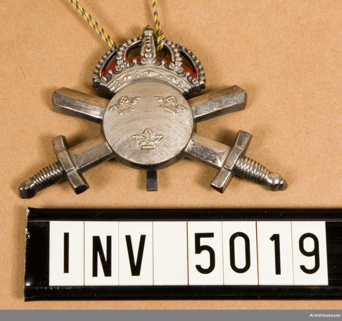 Ubfl. I 1, I 4, K 1, P 1, trängtrupper. Tillverkat av metall och för ovanstående förband i silverfärg. Utgöres av två korslagda svärd, rödfodrad krona samt knapp m/1939-60 i guldfärg.