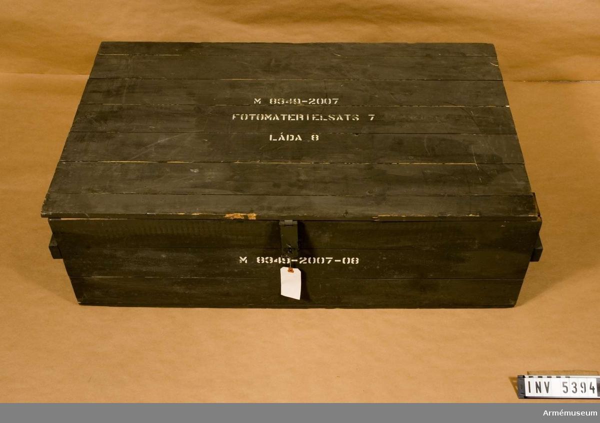 Förvaringslåda av grönmålat trä. Märkt med vit text, framställd  med schablon: M8349-2007-8.
