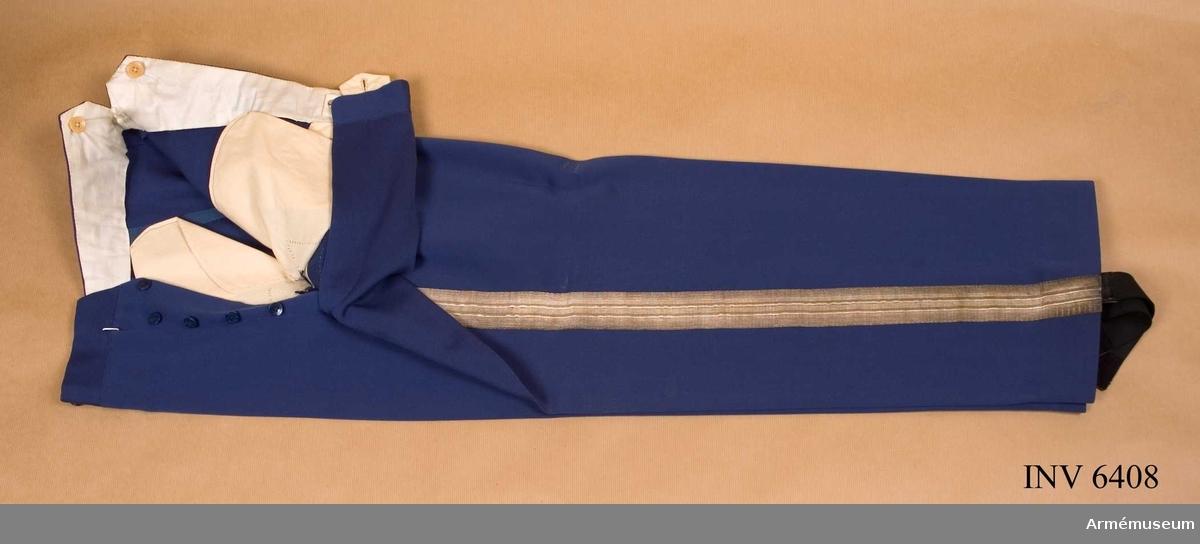 Stl B 50. Av kamgarnssatin nr 3, mellanblå, något ljusare färg. Fyrtio mm bred silvergalon längs yttersömmen.