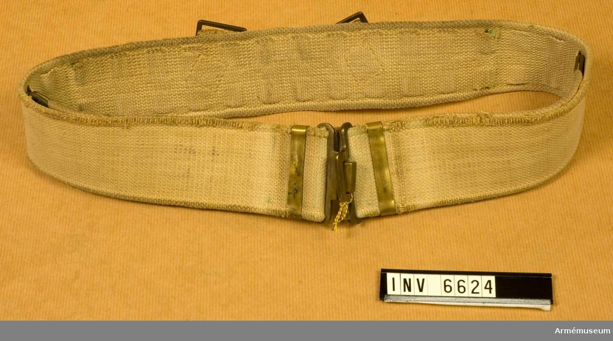 Av textil. Bredd: 60 mm. I ljust grön textilväv med hakspänne i gulmetall. I ryggen  påsydda hankar för tillbehör.