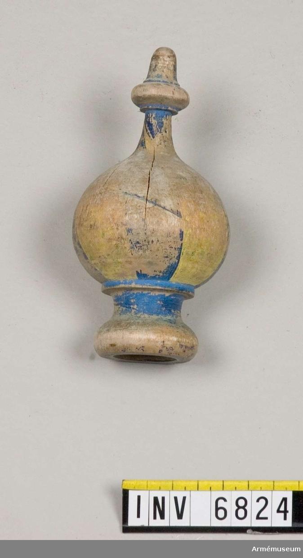Mått: 120 mm hög, 45 mm vid basen. Knoppen har ursprungligen varit blå och gulmålad. Nu finns bara knappt synbara spår av detta. Ett hål löper rätt igenom knoppen. I detta skall mittstångens järnten löpa och hålla  knoppen på plats.
