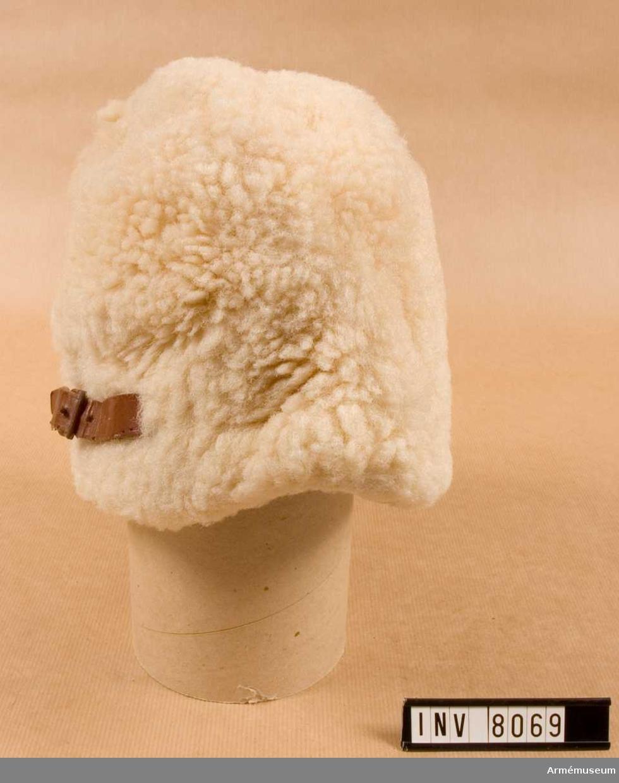 I vitt fårskinn. Höjd 170 mm.  Vidd 610 mm. Vikt 300 g. Fodret är vadderat och har en utvikbar skärm att användas vid behov. Baktill har mössan en rem för reglering av vidden. Kronmärkt i fodret. Storlek 58.