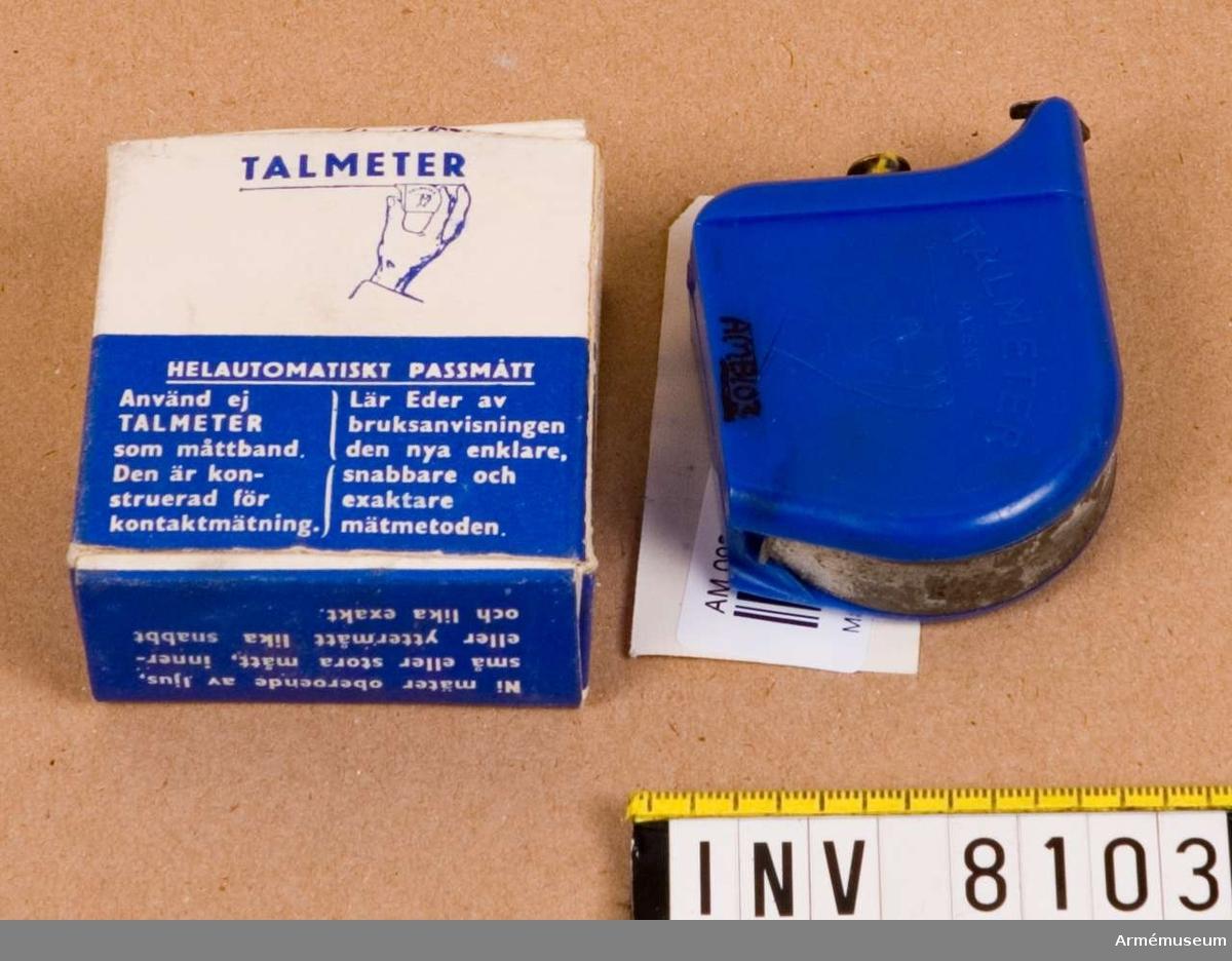 """Tillverkad av blå plast och måttbandet av stål. Kåpan är märkt  med """"Talmeter patent"""" och på motstående sida """"T. A. LJUNGBERG SWEDEN"""". Bandets längd är 2 m. Bruksanvisning finns i  förpackningen.Ingår i fotomaterielsats 7 låda 1."""