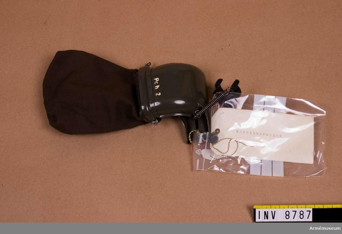 Hylsfångare t kulsprutepistol m/1945. Modellexemplar:Märkt: L & L 1958. Pch 2. Etikett med bly-sigill, märkt AKGf.Hylsfångare består av: Hylsavledare, klämring, fästklack och hylspåse av väv. Se Soldatinstruktion för armén Materiel 1969. sid. 56-57..