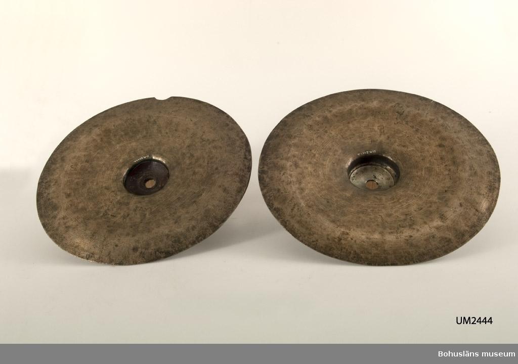 Cymbal eller bäcken är ett slaginstrument.  En rund, konvex metallplatta. Den ena av cymbalerna (a) har en läderskiva på baksidan av den s.k. klockan (föremålets mittpunkt). I den andra syns en annan slags metallskiva fastnitad.  Skador - sprickor, delar borta på båda klockorna och på den ena cymbalens kant. Troligtvis saknas någon fom av läderhandtag som kanske stuckit ut genom hålet i mitten. På a finns rester av tryckta texter på metallen. Tyvärr går inte informationen att tyda.  Oftast slår man på instrumentet med trumstockar. Cymbaler kan också användas två och två då de slås mot varandra för att skapa ljud; kallas då parcymbaler eller bäckar.  Ur handskrivna katalogen 1957-1958: Ett par cymbaler a) D. 34,5 cm; i centrum trasig och lagad, i kanten ett halvrunt urtag; b) D. 34,3 cm; i centrum trasig och lagad.
