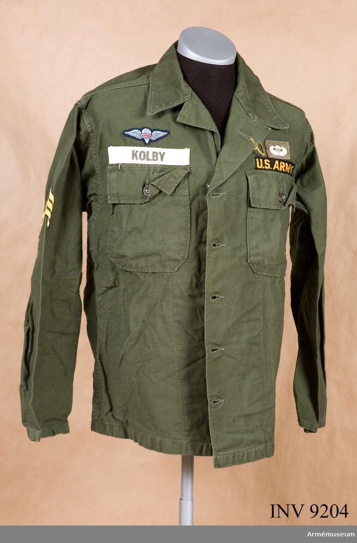 """Skjorta, fallskärmshoppare, Special Forces, US. Tillverkad av grönt satinvävt bomullstyg. Har två bröstfickor med lock och knäppning. Schillerkrage och ärm utan manschett. Ovanför vänster ficka ett grått märke med en vit fallskärm med vingar för Parachutist (fallskärmshoppare). Under detta märke ett svart band med texten: """"US ARMY"""" i gult silke. På höger sida ett fallskärmsjägarmärke med texten: """"RIGGER"""". Under detta på vitt band står med grå bokstäver """"KOLBY"""". Skjortan eller jackan knäpps med vanliga knappar. Källa: Army Badges and Insignia since 1945 Book one. Blandford colour Series."""