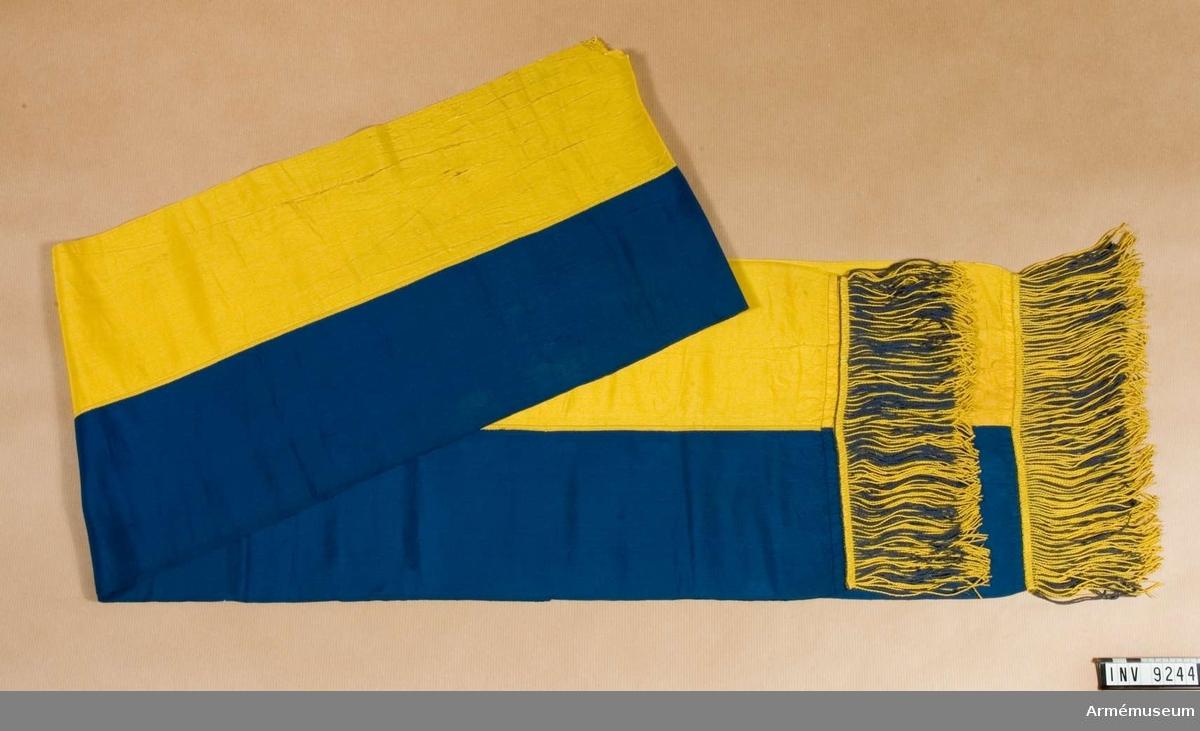 Fanband (kravatt) m/1899.Två längder av ripsband, det ena gult, det andra blått, är ihopsydda på längden. I de båda ändarna sitter en dubbel frans med blandat gult och blått silke. Stadkanten på bandet är gult.