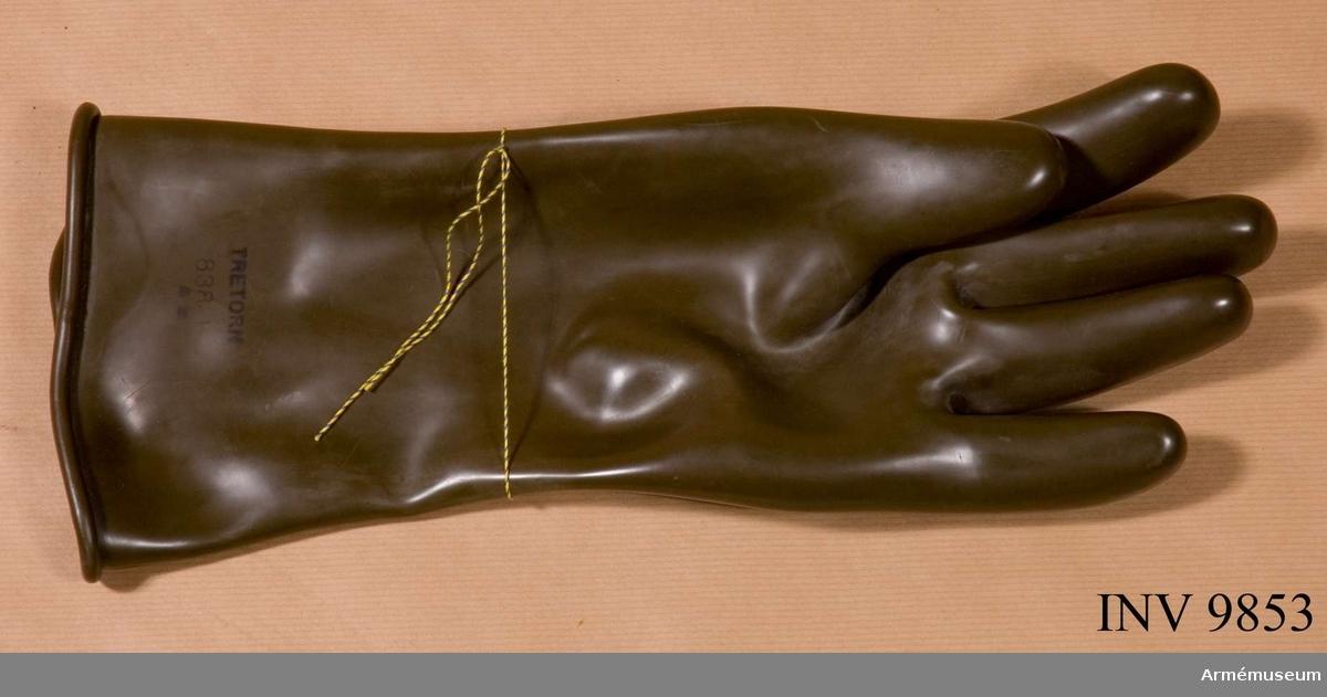 """Skyddshandske, 1950-tal, vänster. Skyddshandske, vänster hands, från 1950-talet. Handsken är märkt """"Tretorn 838-4"""". Handsken är till färgen grön och avsedd att användas till skyddsdräkt M 7376-701011 skyddsdräkt 701/S.Handsken inlånades till utställningen """"Rustning Utrustning"""" 1981."""