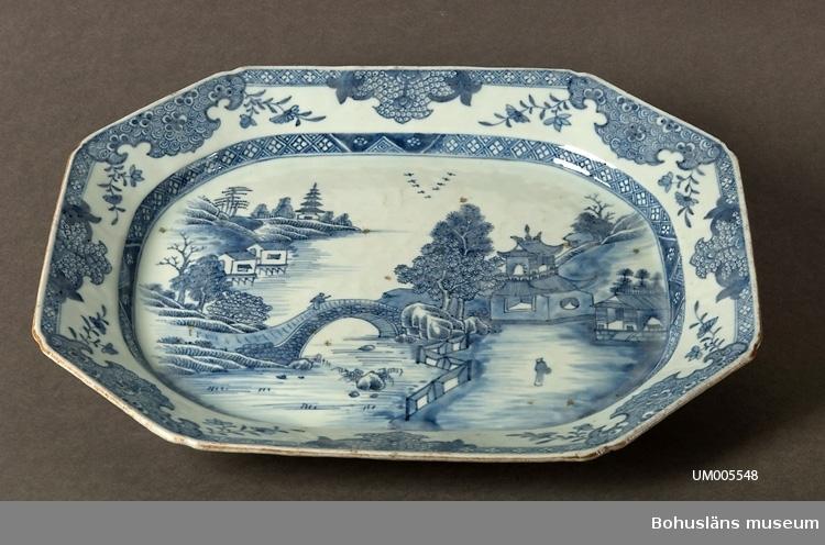 Ur handskrivna katalogen 1957-1958: Stekfat, Ostind. L. 37,3 Br. 30. 8-kantigt fat. Vitt porslin med blom- och landskapsmönster i blått. Helt.  Lappkatalog: 62