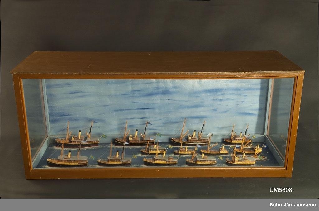 """John Emil Olsson var från år 1913 anställd i Bohuslänska Kusten, först som styrman på Robert Thorburn och Kung Rane och från 1930 som befälhavare på Victor, Byfjorden och Robert Thorburn. På denna post kvarstannade har till år 1945 så han avgick med pension.  Textat på monterns botten/målade havsyta: """"ÅNGFARTYGS.AB. BOHUSLÄNSKA - KUSTENS PASSAGERARE & LASTFARTYG 191?-talet"""". 16 modeller.  Ur handskrivna katalogen 1957-1958: Bohusl. Kustens flotta 1918 Modeller över flottan i glasmonter. Föremålen hela. Från kapten Olssons saml., Fiskebäckskil.  Se Bilagepärmen UM005808, UM005814 och UM024652 för foton. För ytterligare information om förvärvet, se UM005807."""