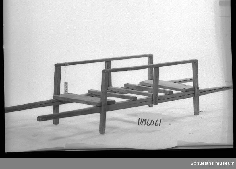 Ur handskrivna katalogen 1957-1958: Bår L. c:a 250 cm. H.: 54 cm. Låga ben, på långsidorna låga skrank av tre ståndare o en stång. Omålad. Hel.  Lappkatalog: 94