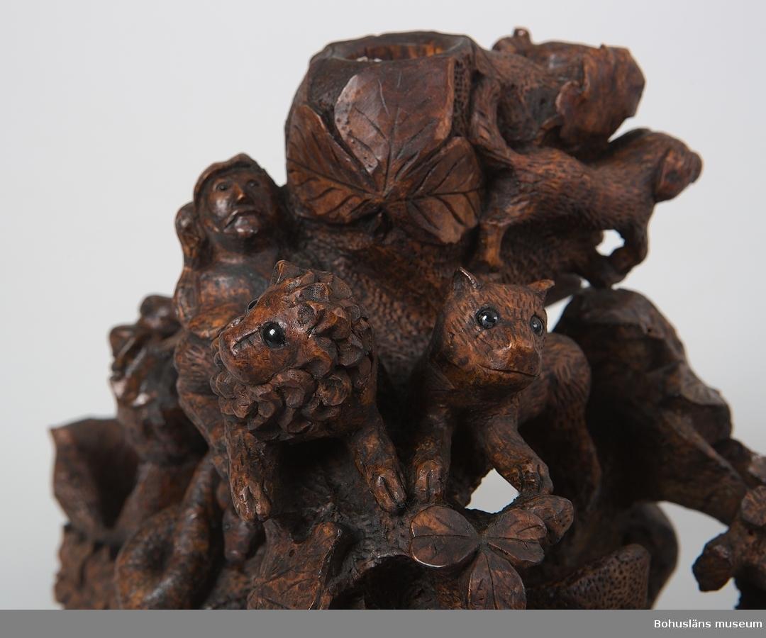 """Sockel med täljda figurer skurna i en rot från ett lövträd (al, björk, rönn ...). Elva djur och två människoliknande varelser syns i """"ett stubbliknande landskap"""" med vegetation i form av löv liknande de från rönn eller stensöta, vinranka och klöver. Bland djuren hittar man krokodil, orm, lejonhane, lejonhona, hundar, möss, ett klövdjur, kanske något slags får samt en fågel. Djuren har ögon av svart glas. I ett urtag mitt i sockeln är en spegel i ram med utskuret dekorativt mönster samt krön av vinranka med två små druvklasar placerad. Ramen har ytbehandling i ljusare gult; övriga delar har en yta som är mörkt brunfärgad troligen av schellack. Spegelram och ställning gjord i lövträ, troligtvis björk, bakstycke är gjord av ett träskiva av furu som noggrant passats in i ramen. Hantverkaren som utfört snideriet har haft tillgång till många olika typer av verktyg.  Flyghål efter insektsangrepp i sockeln.  Ur handskrivna katalogen 1957-1958: Spegel med naturalistiskt utformad sockel Totalhöjd: 61 cm. Spegeln oval, rörligt upphängd i en hästskoformad ställning. Sockel med djur och dekorativa löv. Av utsnidat trä. (Relativt hel.)"""