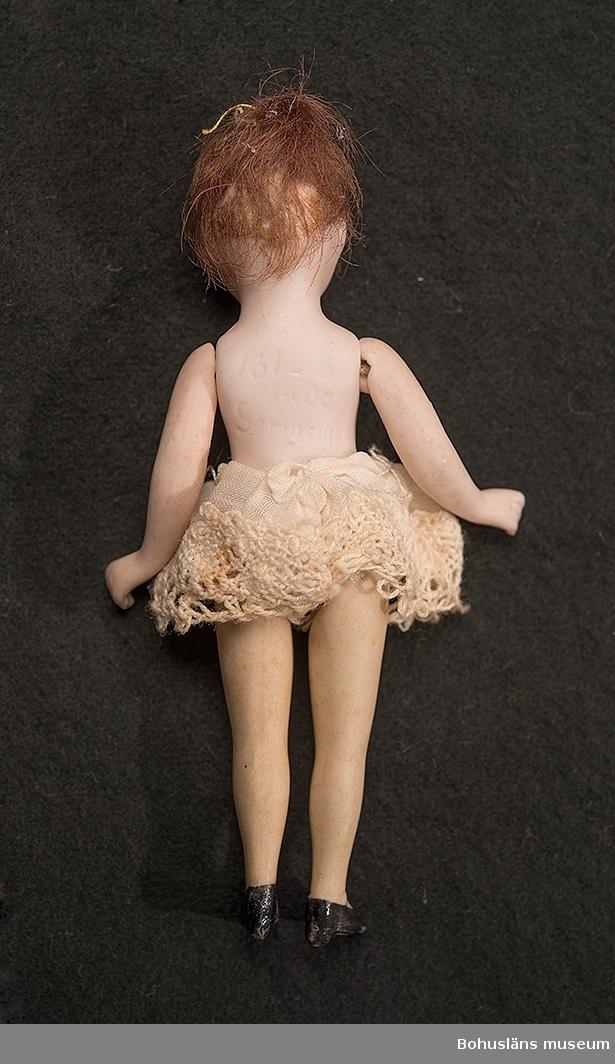Docka i porslin med lösa armar och ben. Dockan är försedd med brunt hår, blå ögon bruna ögonbryn. Svarta skor med slejf. Benkläder med spets. På ryggen är intryckt 161-8. Övrigt oläsligt. Armar och ben är sammanfogade med gummiband som av ålder har mist sin spänst.