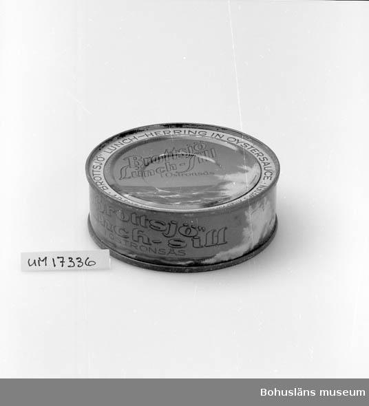 """Föremålet visas i basutställningen Kustland,  Bohusläns museum, Uddevalla.  Rund blå burk. Påfalsat lock och botten. Blå och röd text: """"Brottsjö lunch-sill i ostronsås. Brottsjö lunch Herring in oystersauce A-B. Elis Luckeys Konservfabrik, Sweden"""". På sidan: """"Brottsjö lunch-sill i ostronsås A-B.  Elis Luckeys Konservfabriker A/S Lysekil - Köbenhavn"""". Se UM17232."""