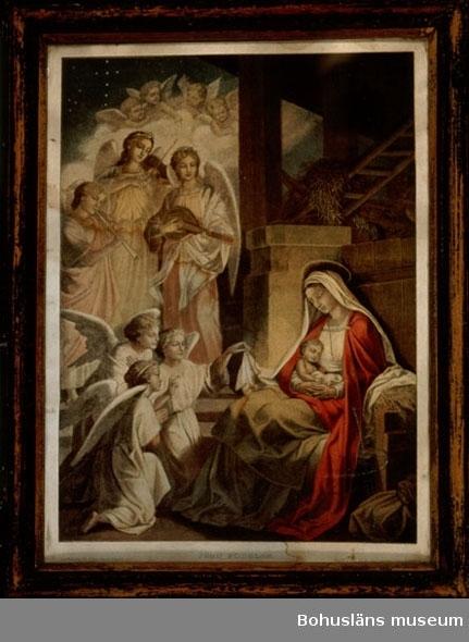 """594 Landskap BOHUSLÄN  Bild av Jungfru Maria och Jesusbarnet i stallet och tre tillbedjande änglar och tre spelande  änglar (flöjt, fiol, luta) samt fyra amoriner på moln. Färgtryckt xylografi? Inramad med glas och träram med starkt sliten svart färg. Text: """"Jesu födelse"""". Konstbilaga till Allers familjejournal. Tryckt i Carl Allers etablissement, Köpenhamn""""."""