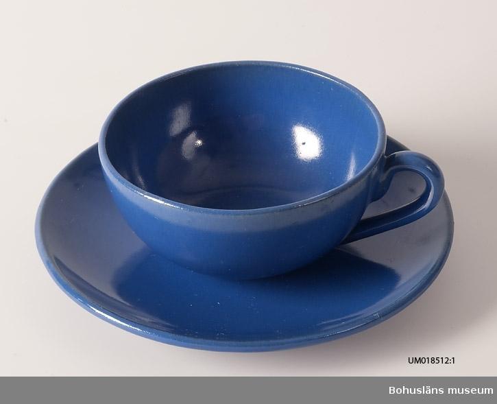 Närmast halvsfärisk tekopp med fat. Klart blå glasyr. Ingen dekor. Både koppens och tefatets botten stämplad svart: SYCO.