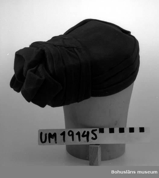 Föremålet visas i basutställningen Uddevalla genom tiderna, Bohusläns museum, Uddevalla.  394 Landskap BOHUSLÄN  Brun hatt bestående av draperat tyg. Kullen har en fyrkantig valk fastsydd framtill och en rosett av tyget. Foder av taft.  Se UM19130.