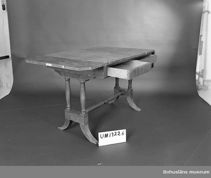 471 Tillverkningstid 1840-TAL  Bord med fällbara klaffar i Karl Johans-stil. Salongbord med två lådor inunder skivan. Faneren skadad på några ställen. Benen hopkopplade men 23 cm över golv är de sedan utsvängda ner till golvet.