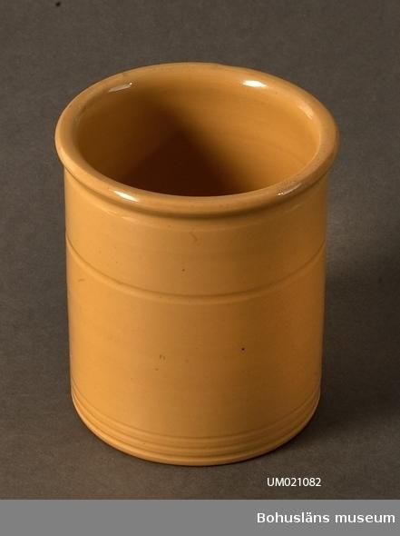 Gul färg, tre ränder vid botten och en längre upp över mitten. Upptill svagt utvikt kant. Eventuellt tillverkad av Höganäs Keramik, Sverige, under 1900-talets första hälft.