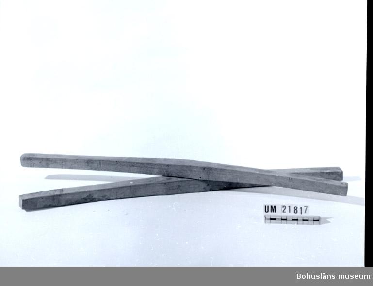 Huvudet till en räfsa. Avlångt, något bågformat trästycke med fyrkantig genomskärning. På den ena är det markerat var skaftet skall fästas. På den andra står det något skrivet med blyerts. Ämne till handredskap för att räfsa hö med.