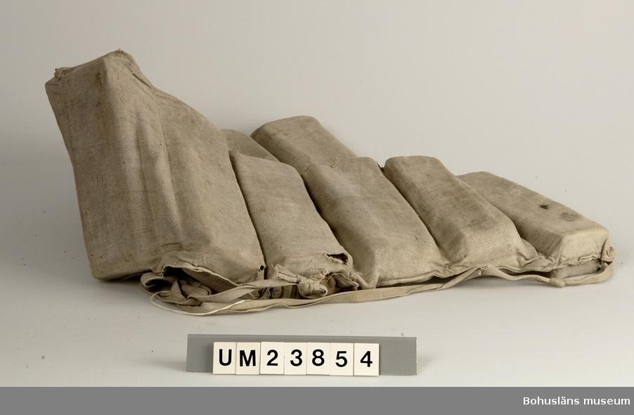 Föremålet visas i basutställningen Kustland,  Bohusläns museum, Uddevalla.  Livbälte bestående av tio stycken 25 x 8 x 5 cm stora korkplattor, insydda i fack i ett bälte av ofärgat, grovt tuskaftsvävt bomullstyg. Försedd med axelremmar i samma  tyg. Har eventuellt använts av sjöscouter.