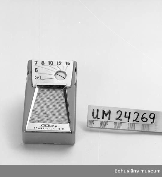 """Minitransistor. Märke: """"Charp Transistor Six"""" av japansk tilverkning. Ljusblå plast. Högtalare på framsidan. Ett """"snurrhjul"""" på varje  långsida, ett för avstängning och påsättning. Det andra för att söka  kanaler. Batteridriven. Uttag för hörlurar."""