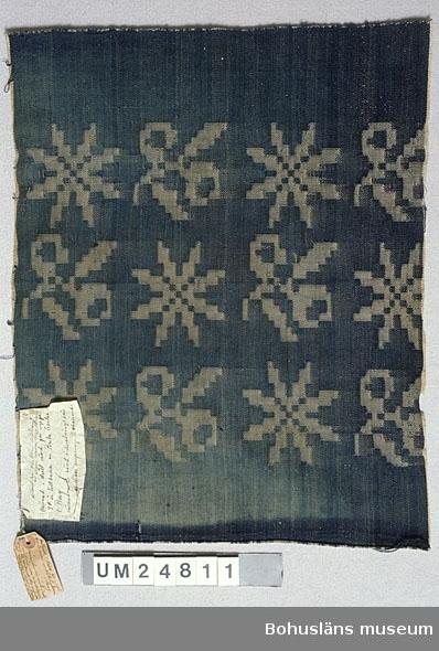 """Vävd i damast, gjord i vävstol med sk dragrustning. Benämningen dräll används nu (1990-tal) till vävnader med enkla geometriska mönster, ofta rutor, vävda i vanlig skaftvävstol utan extra anordningar för mönsterbildning. Provbiten har vit bomullsvarp och blått inslag som troligen är av bomull men möjligen slitet lin. På rätsidan framträder vita stjärnor och stiliserade blommor/blad mot blå bakgrund. Grundbindning: Korskypert. Vävd med 2 tr tillsammans både i varp och inslagsriktning. Två pappersetiketter fastsydda. Text på etikett 1: """"Skänkt till fru Karin Kleberg av Signe Olsson, Berg, Ödsmål  Vävnad i dräll vävd för ungefär 40 år tillbaka av Brita Carlsson i Berg vävnaden är vävd i rustningsväv men mönstrets ursprung är obekant."""" Text på etikett 2: """"Vävnad i dräll för ungefär 40 år sedan av Brita Carlsson i Berg. Vävnaden är vävd i rustningsväv, men mönstrets ursprung är obekant. Har använts till möbeltyg. Skänkt av Signe Olsson Berg Ödsmål till Karin Kg."""" På etikett två även: """"maj 1923"""" """"maj 6063 1913"""". Dateringen gjord utifrån de årtalen. Ytterligare uppgifter om gåvan UM24798 - UM24 883, se UM 24798. Januari 2002: Enligt Berit Eldvik, Nordiska museet, finns både kvisten och stjärnan som liknande mönsterformer att hämta i """"Afhandling om drällars och dubbla golfmattors tillverkning"""", J. E. Ekenmark och systrar, Stockholm 1828. / MJ  Enligt uppgifter vid studiebesök från textilintendent Berit Eldvik, Nordiska museet,  är mönstret sannolikt hämtat ur någon av de tiotal handböcker i mönstervävning som publicerades mellan åren 1826-1843 av vävarfamiljen Ekenmark från Östergötland.   Uppgifterna kompletterade 2002-01-30 A-LS"""