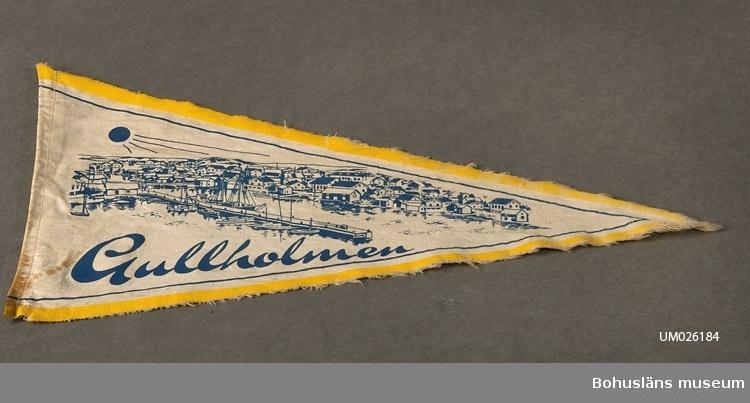 """Trekantig vimpel. Mot naturfärgad grund textiltryck i blått med utsiktsbild över Gullholmen (Bohuslän) samt namnet """"Gullholmen"""". Gul kant. En fållad sida, de två andra skurna. Sammanhör med UM026180-UM026184 Användnings- och förvärvsuppgifter se UM026180"""