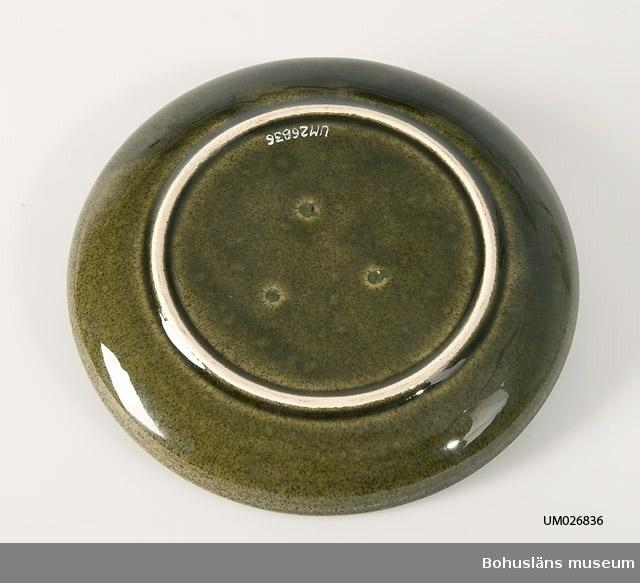 Assiett av keramik glaserad i melerat mörkt gröngult med brunt inslag. Slät, uppböjd kant ytterst. Hör samman med kaffekopp UM26835, gräddkanna UM26837 och sockerskål UM268388. Ytterligare uppgifter se UM28835.