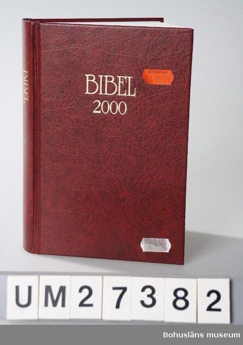 """Bibel inbuden i rött konstläderband med texten """"BIBEL 2000"""" i nedsänkt guldrelief på framsida och rygg.  Bibelns text är  i nyöversättning, den tredje med officiell karaktär. Huvudsyftet är att vara huvudtext för bibeln inom det svenska språkområdet. De båda tidigare översättningarna utgavs 1541 och 1917. Bibelns grundtexter skall här översättas till nutida svenskt språk. Bibekommissionen tillsattes 1972 och avslutar sitt arbete i och med utgången av år 2000. Texten i denna bibel godkändes av Bibelkommissionens styrelse 1999. Avslutande historisk presentation i fyrfärg av bibelns originalspråk, skriftspråk,  tidsaxlar,  karta, arkitektur, högtider, betydelsefulla personer i Gamla och Nya testamentet, vardagsliv i bibels länder, innehållsöversikt m.m.  Text på försättsbladet: """"BIBEL 2000  GAMLA TESTAMENTET APOKRYFERNA NYA TESTAMENTET Bibelkommissionens översättning  Marcus Förlag""""  Inköpt  för 149 kronor, extrapris.  För information om Millennieinsamlingen, se UM27360."""