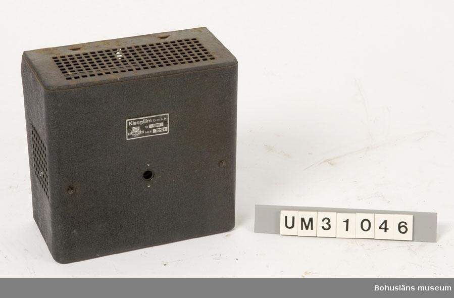 Elskåp av svart brännlackerad plåt för väggmontering med oklar användning, kanske  till ljudanläggningen. Kan det vara förstärkare till en högtalare?  Rektangulär låda märkt med metallskylt: KLANGFILM G. m. b. H. Runt hål för liten kontakt placerad mitt fram.   Skåpet har använts tillsammans med  projektor UM31031.   Projektorn är tillverkad av AEG på 1920-talet och har använts i Folkets Hus i Sjöbol vid Lysekil.  Till projektorn hör en lång rad delar och olika tillbehör, UM31031 - UM31062.  För ytterligare upplysningar om filmprojektorn, dess olika delar och användning, se UM31031.