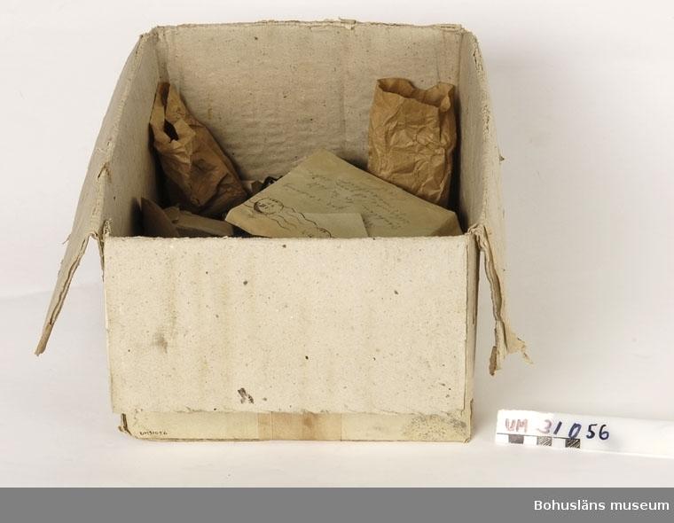 Pappkartong med diverse utrustning till filmprojektor och annan teknisk utrustning,  bl. a kolstavar, papperspåsar med säkringar, plåtask med reservdelar, sandpapper, en fil, pappkartong med muttrar och skruvar, bakelitvred och bakelitkontakter samt ett kuvert adresserat till: Sjöbo Folkets Hus Förening Lyse med avsändare: GASACCUMULATOR STOCKHOLM LIDINGÖ Poststämplat 21.9.1951 med 25-öres frimärke, på baksidan antecknat med bläck: Sven gör iordning ventilen för vi fått åläggande att göra detta omedelbart Evert!  På kartongens ovansida fastklistrad adresslapp med texten: A-B KINOFA, Hammarbyvägehn 9 - 11 ILGODS från Stockholm Sö. Station Till Folkets Hus Sjöbol Lyse  Materialet använts tillsammans med  projektor UM31031.   Projektorn är tillverkad av AEG på 1920-talet och har använts i Folkets Hus i Sjöbol vid Lysekil.  Till projektorn hör en lång rad delar och olika tillbehör, UM31031 - UM31062.  För ytterligare upplysningar om filmprojektorn, dess olika delar och användning, se UM31031.