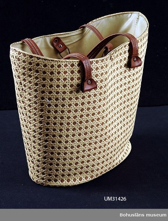 Fodrad oval damväska av beige plast, imiterande flätad bast med två korta handtag i brun plast. Väskan användes som badväska och shoppingväska. Se fotografi, UMFA55058:0001.  Föremålet har använts av familjen Abrahamson i deras sommarstuga i Sundsandvik, byggd 1939. För ytterligare upplysningar om förvärvet, se UM031385.