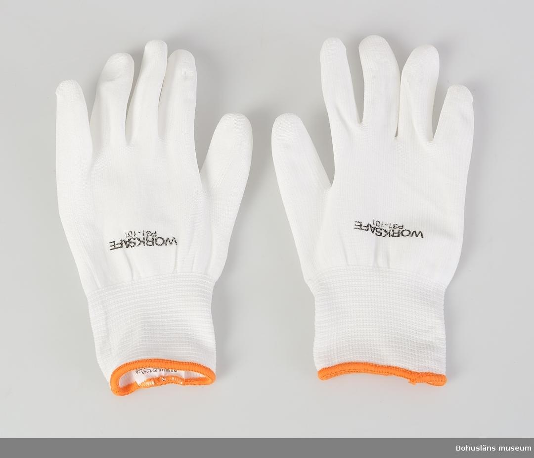 """Vit sömlös PU-belagd (polyurethane) elastisk nylonhandske. På ovansidan med tryckt text WORKSAFE P31-101. Orange handledlinning. För finmonteringsarbeten. På insidan produktetikett med symbol för kravuppfyllnad """"Skyddshandskar mot mekaniska risker"""". I produktblad med följande beskrivning: """"Handskar för alla jobb som kräver maximal fingerkänsla. Worksafe P31-101 är belagd med PU, vilket ger ett bättre grepp och gör den även vattenavvisande. Handsken är helt sömlös, inget i handskarna skaver eller irriterar. Den stickade nylonlinern är mycket elastisk och handskarna sitter nästan som en yttre hud. Lämplig för: Montering, inspektion, packning och lagerarbete. Bästa fingerkänslan Bästa passform Slitstark Utmärkt torrgrepp Vita, oönskad smuts syns direkt Utan sömmar Elastisk Silikonfri"""