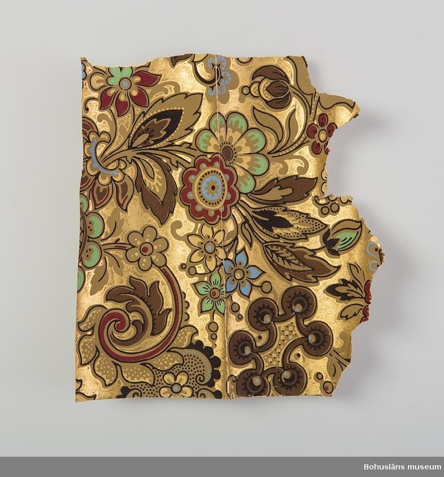 Fragment av papperstapet från 1890-talet från Slottet på Stenungsön, Stenungsund.  Blommönster i brunt, blått, gult och svart på guldfärgad botten.