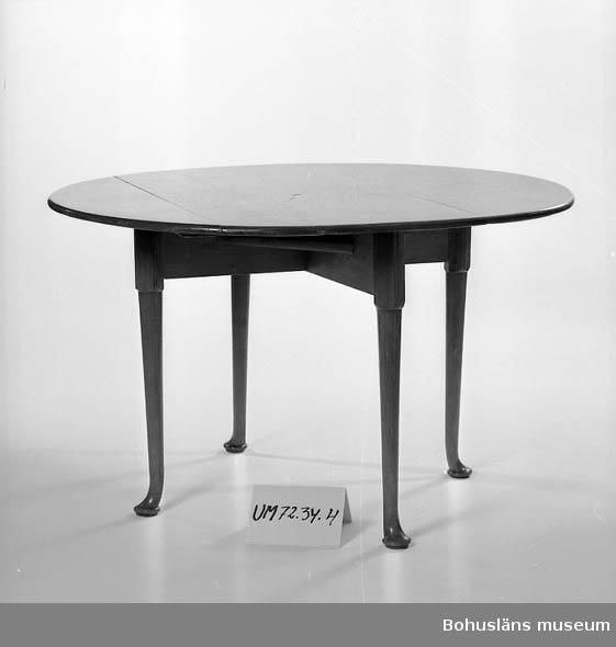 Bord på kryssformig underdel, runda ben med nertill mjukt utsvängda fötter. Bordskiva med uppfällbara klaffar. Bordsskivan är rektangulärti nedfällt läge, rund i uppfällt läge. Skivan vrids när den skall fällas upp. eller ned.  Ur verksamhetsberättelse 1972 för Uddevalla museum: Några verkligt goda möbler från 1800-talets mitt, en soffa, två karmstolar, ett bord och en med pärlemor- och metallinläggningar rikt dekorerad chiffonjé, har s. a. s. återbördats till Uddevalla. Givare är fru Ida Koch, Stockholm, som därmed enligt egen utsago kunnat uppfylla sin 1953 avlidne makes, lektor Carl O. Koch, av den kända uddevallasläkten, uttalade önskan.  Möblernas ägare, Carl Olof Koch, föddes 1877 på Vågsäters gamla bruksherrgård och före detta järnbruk i Valbo-Ryrs socken i Munkedals kommun i sydvästra Dalsland. Han var son till brukspatron Carl Simson Koch (1829-1886) och Martina Elisabeth Fröding  (1836-1912).  Från 1700-talet drevs här järnmanufaktur med tegelbruk, såg - och kvarnverksamhet. Familjen Koch drev även Liljenfors bruk. Gården hade även stora åker- och skogmarker. Egendomen köptes på 1780-talet av Simzon Koch (1757-1822) och ägdes av familjen till 1877.  Simzon Koch var son till Michael Koch (1715-1789), borgmästare i Uddevalla. Simzon Koch hade tidigare drivit familjens gamla manufakturer vid Kollerö, Rådanefors och Öxnäs tillsammans med sin bror, Erik Koch och fadern under Koch & Söner. Simzon Kochs son Mikael Koch d. y. (1792-1869) och sonsonen Carl Simzon Koch (1829-1886) drev Vågsäter vidare. 1877 förvärvades egendomen av Munkedals Aktiebolag.  Litteratur: Kristiansson, S: Uddevalla stads historia, del II och III. Uddevalla 1953 och 1956.